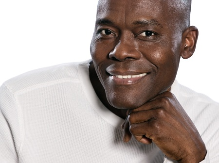 un homme: Close-up portrait of an afro American mature man smiling with hand on chin in studio on white isolated background Stock Photo