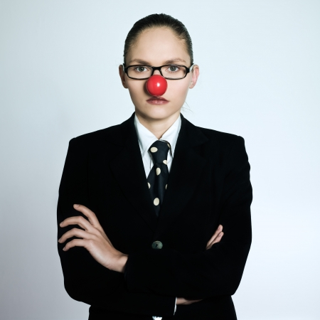 studio shot portrait of a beautiful one young business woman in a costume suit with a clown nose on isolated grey background photo