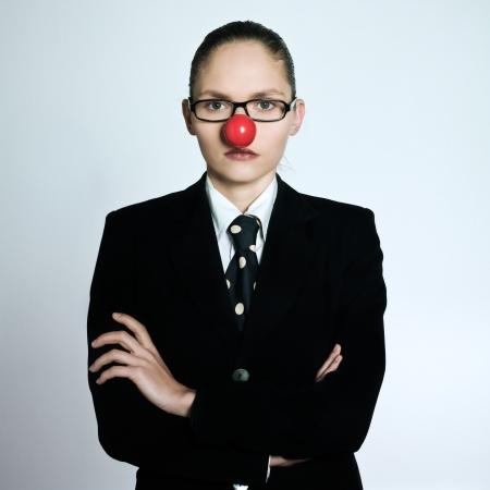nez de clown: tourn� en studio portrait d'une belle une jeune femme d'affaires dans un costume costume avec un nez de clown sur fond gris isol�