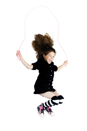 kids dress: caucasian little girl jumping skipping rope isolated studio on white background