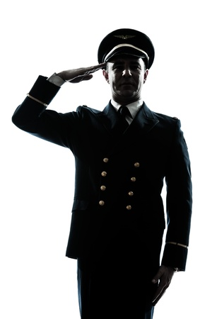 a l ecart: one caucasian man in airline pilot uniform saluting silhouette  in studio isolated on white background