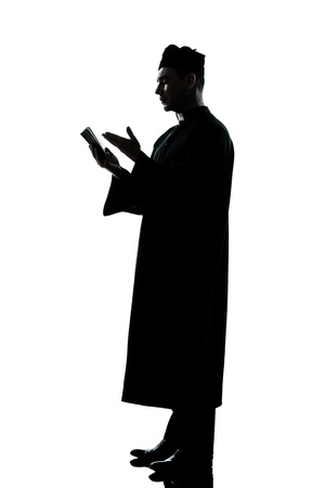 a l ecart: one caucasian man priest reading bible silhouette in studio isolated on white background