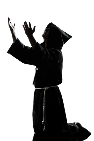 a l ecart: one caucasian man priest praying silhouette in studio isolated on white background Stock Photo