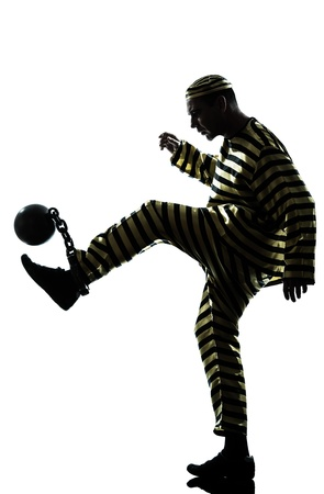 a l ecart: one caucasian man prisoner criminal playing soccer with chain ball in studio isolated on white background