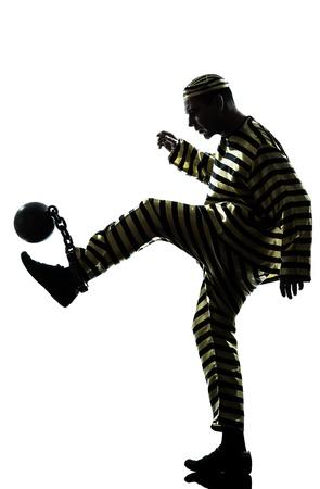 preso: un hombre caucásico preso común jugar al fútbol con la pelota de la cadena en el estudio aislado sobre fondo blanco Foto de archivo