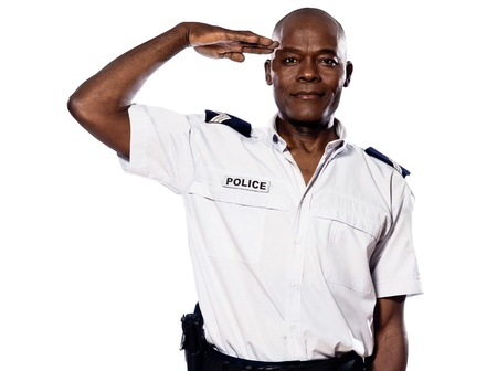 regards objectifs: Portrait of an afro American policeman saluting in studio on white isolated background