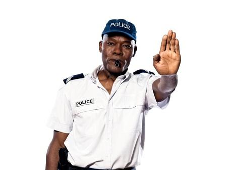 gorra polic�a: Retrato de un oficial de polic�a afro americano que hace un gesto de parada en el estudio sobre fondo blanco aisladas