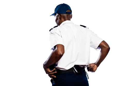 security laws: Rear view of afro American police officer pulling out handcuffs in studio on white isolated background