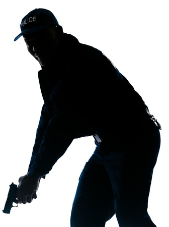 Silhouetted image of afro American policeman holding handgun in studio on white isolated background photo