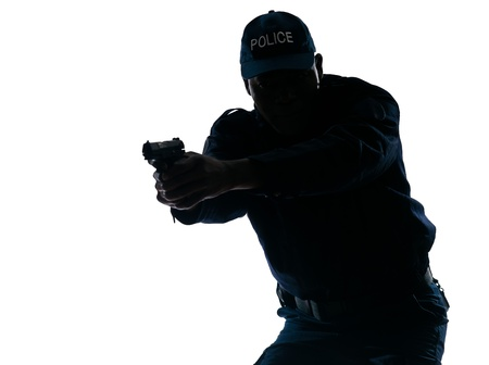 security laws: Silhouetted Afro American police officer aiming handgun isolated on white background Stock Photo
