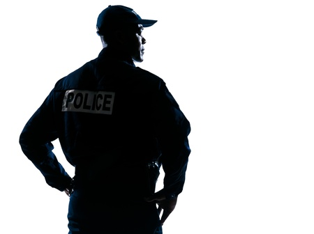 security laws: Rear view of a serious afro American policeman with hands on hip looking to his side on white isolated background