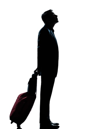 a l ecart: one caucasian man business traveler waiting looking up full length silhouette in studio isolated white background