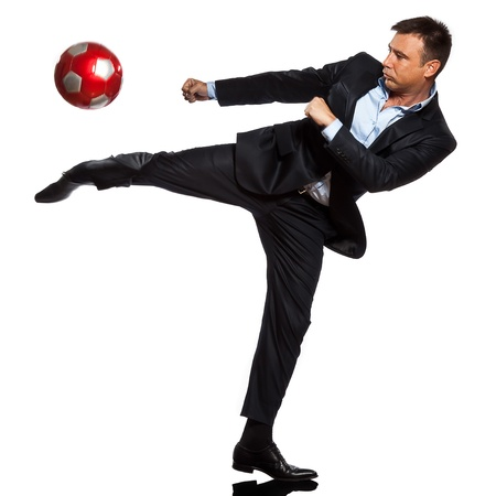 kicking ball: one caucasian business man playing kicking soccer ball in studio isolated on white background Stock Photo