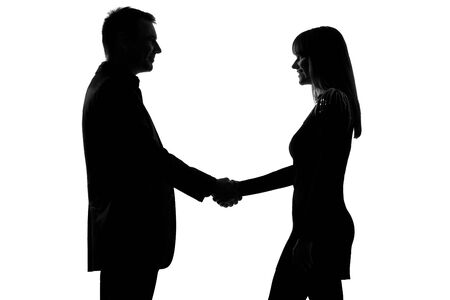 one caucasian couple man and woman handshake in studio silhouette isolated on white background photo