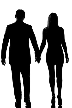 lovers holding hands: rear view one lovers caucasian couple man and woman walking hand in hand in studio silhouette isolated on white background