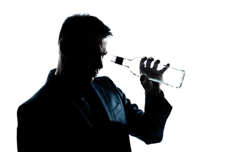 one caucasian man portrait silhouette drunk looking at an empty alcohol botlle in studio isolated white background photo