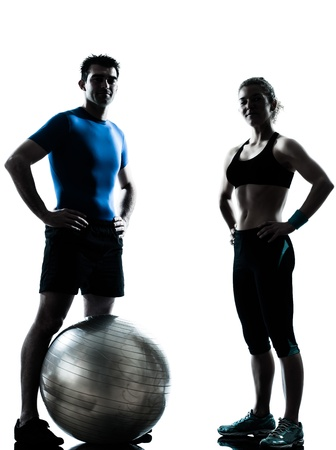 fitness trainer: one caucasian couple man woman personal trainer coach exercising fitness ball silhouette studio isolated on white background Stock Photo