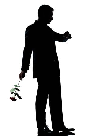 un hombre caucásico que sostiene una flor rosa esperando verificación silueta tiempo de larga duración en estudio de fondo blanco aisladas Foto de archivo