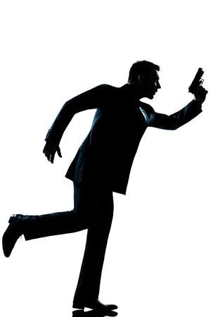 spy criminal policeman detective  man running holding gun full length silhouette in studio isolated white background photo