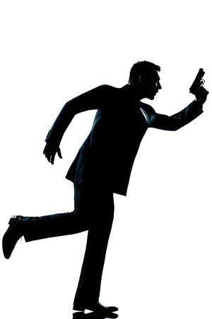 secret service: spy criminal policeman detective  man running holding gun full length silhouette in studio isolated white background