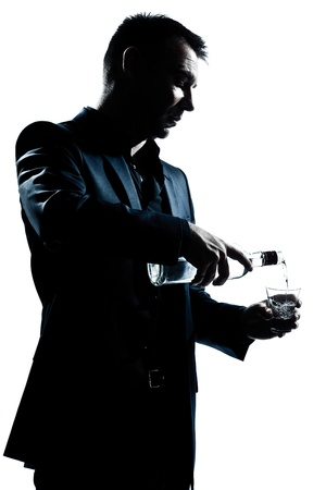 one caucasian man portrait pouring white alcohol silhouette in studio isolated white background photo