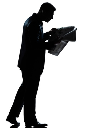 one caucasian man walking reading newspaper  full length silhouette in studio isolated white background photo