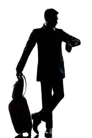 un hombre de negocios caucásico viajero comprobar la silueta de tiempo de larga duración en el estudio aislado sobre fondo blanco Foto de archivo