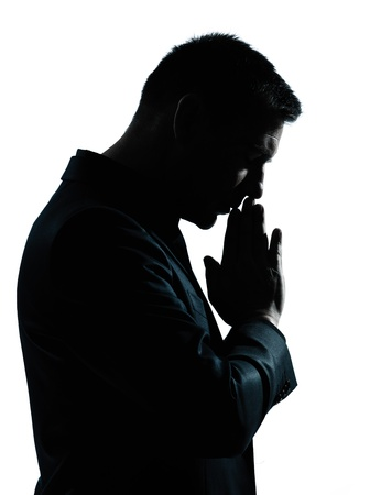 worried executive: one caucasian business man thinking praying  portrait silhouette in studio isolated on white background