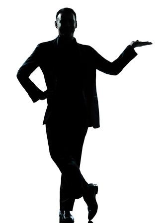 silueta hombre: un hombre de negocios caucásico silueta de pie la mano abierta de cuerpo entero en el estudio aislado sobre fondo blanco Foto de archivo