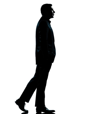 people walking white background: one caucasian business man walking silhouette Full length in studio isolated on white background