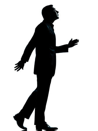 man side view: one caucasian business man walking looking up silhouette Full length in studio isolated on white background