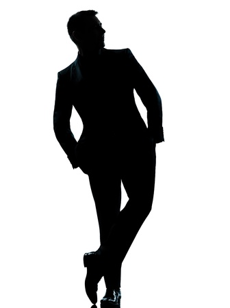 man looking out: one caucasian business man silhouette standing Full length hands in pocket in studio isolated on white background Stock Photo