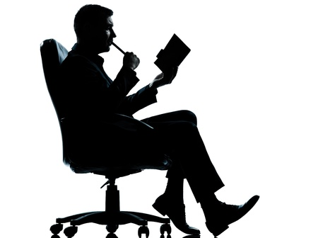 one caucasian business man sitting in armchair silhouette Full length in studio isolated on white background photo