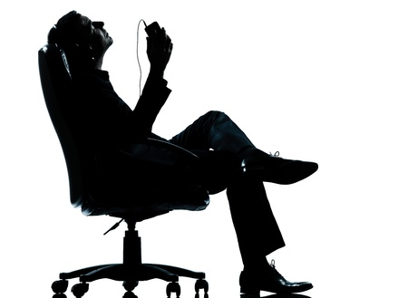 portable mp3 player: one caucasian business man listening music relaxing silhouette Full length in studio isolated on white background