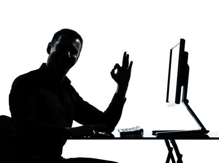one caucasian business man computer computing ok gesture silhouette in studio isolated on white background photo