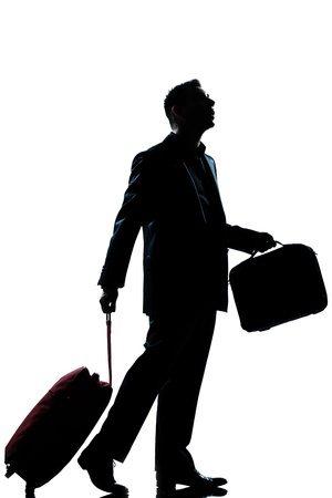 business traveler: one caucasian business traveler man walking with suitcase lost looking up  full length silhouette in studio isolated white background Stock Photo