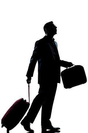 maletas de viaje: un hombre de negocios cauc�sico viajero caminando con la maleta perdida mirando la silueta de cuerpo entero en el estudio de fondo blanco aisladas