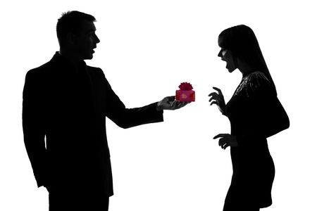 one caucasian couple man kneeling offering present gift and woman surprised in studio silhouette isolated on white background photo