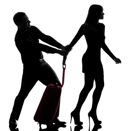 relationship problem: one caucasian couple dispute separation woman leaving and man holding back in studio silhouette isolated on white background