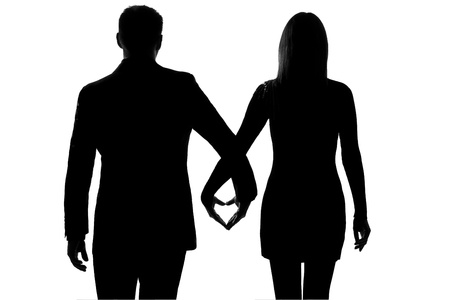 seduction: one lovers caucasian couple man and woman walking hand in hand in studio silhouette isolated on white background