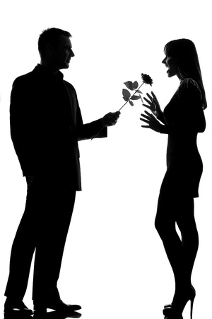 loving couples: one caucasian lovers couple man offering rose flower and woman surprised in studio silhouette isolated on white background Stock Photo