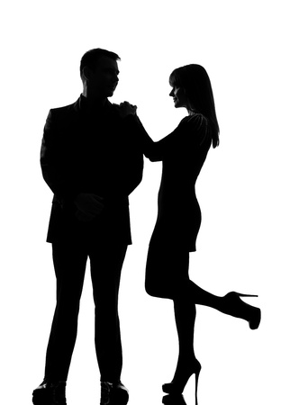 one caucasian couple man and woman standing face to face smiling in studio silhouette isolated on white background Stock Photo
