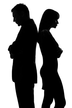 side by side: one caucasian couple standing back to back man and woman sad in studio silhouette isolated on white background