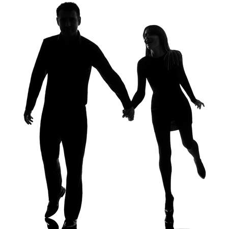 one caucasian couple man and woman running hand in hand in studio silhouette isolated on white background photo