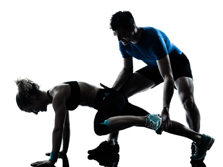 fitness instructor: one caucasian couple man woman personal trainer coach exercising legs silhouette studio isolated on white background