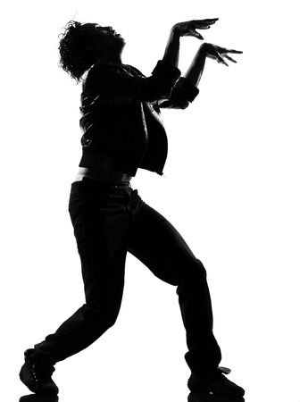 break dancing: full length silhouette of a young man dancer dancing funky hip hop r&b zombie walk on  isolated  studio white background