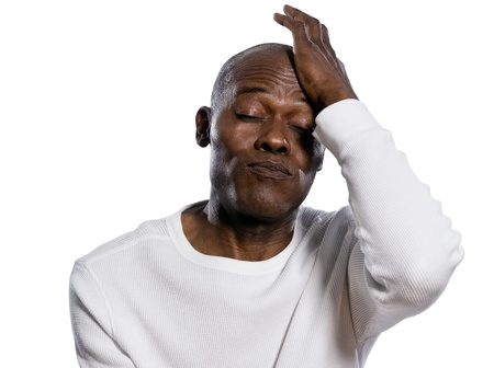 puffing: Close-up of a displeased afro American man with hand on head puffing in studio on white isolated background