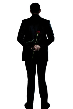'hide out': one caucasian backside man holding a rose flower  full length silhouette in studio isolated white background