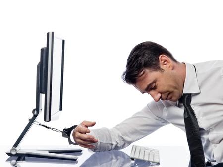 gefesselt: ein kaukasischer Mann angekettet an Computer mit Handschellen Ausdruck Sucht-Konzept isoliert Studio auf wei�em Hintergrund