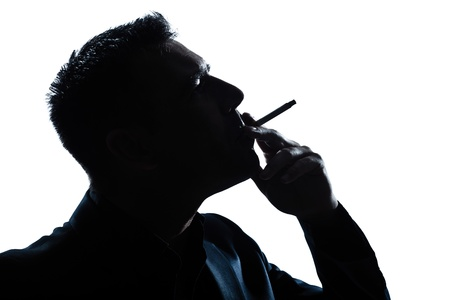 man side view: one caucasian man portrait smoking cigarette silhouette in studio isolated white background